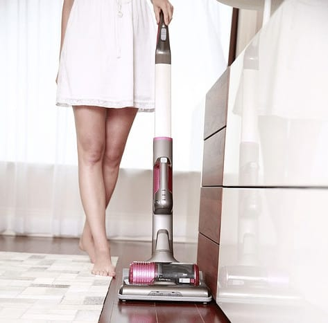 person using vacuum in the wooden floor. Who invented the vacuum cleaner?