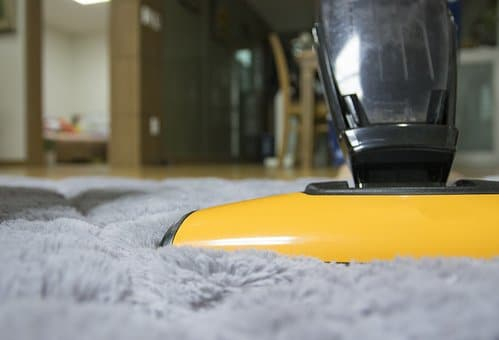 Who Invented the Vacuum Cleaner? Person vacuuming a gray rug